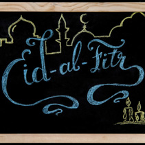 Eid al Fitr greeting hand written with colorful chalk on blackboard