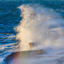 Great wave crushing on breakwater making a rainbow