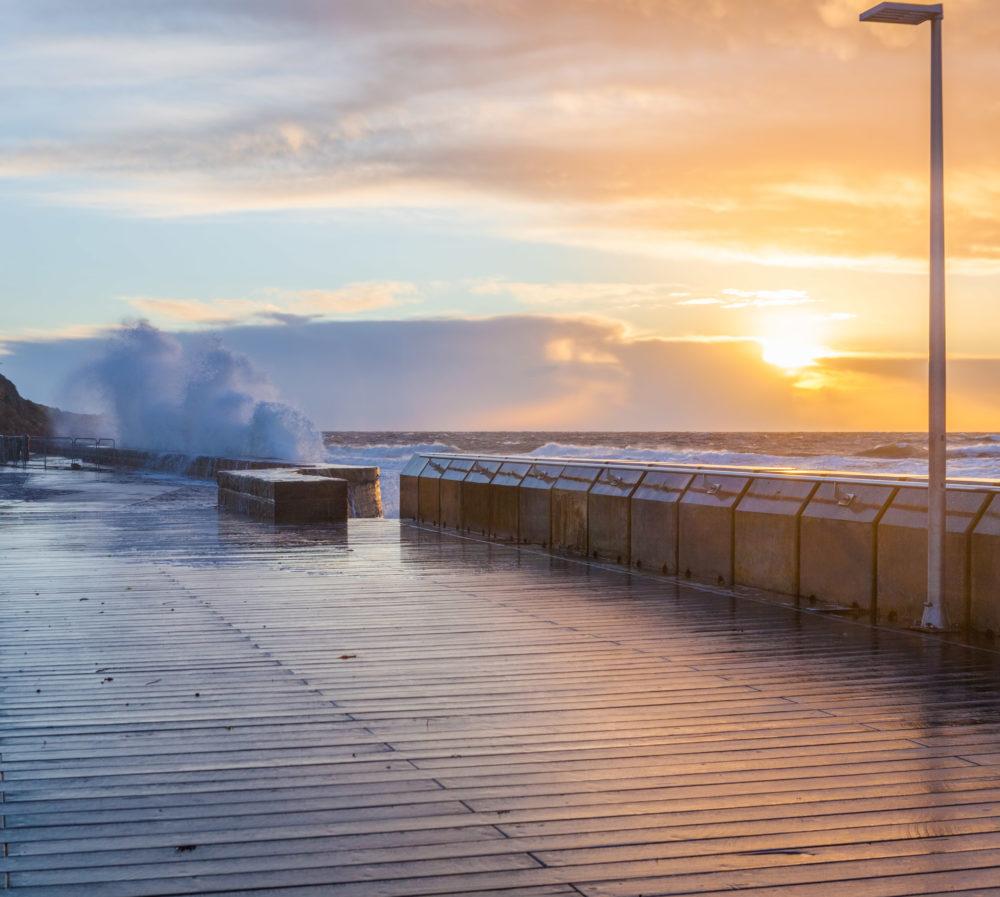 Mornington Pier and big crushing waves at sunset