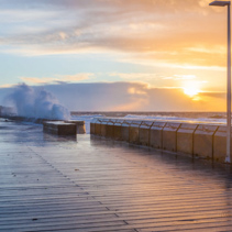Mornington Pier and big crushing waves at sunset