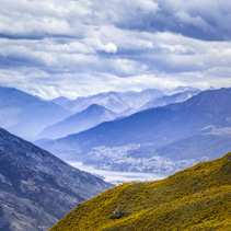 Beautiful orange hills with Queenstown in the distance in faded colors, Otago, South Island New Zealand.