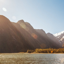Majestic snow capped peaks of Milford Sound with sun flare. Fiordland, New Zealand