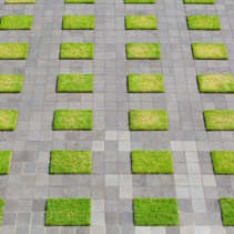 Squares of grass and concrete - modern pavement background closeup