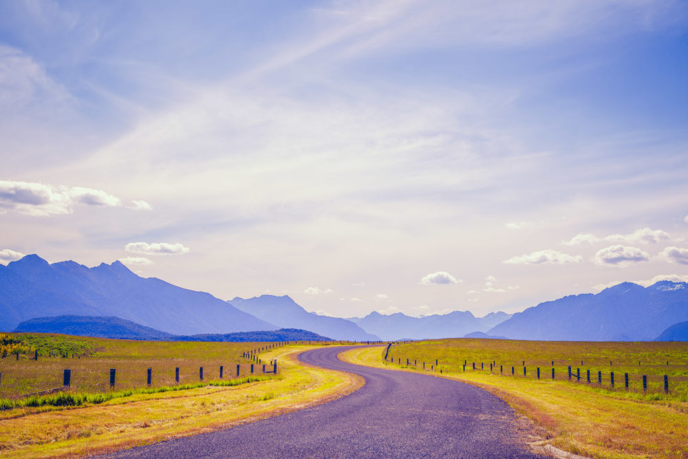 Pastoral winding country road and mountains in Fiordland, South Island, New Zealand