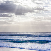 Beautiful seascape with sun rays through clouds and ocean waves