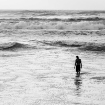 Silhouette of a man standing knee deep in ocean waves in black and white