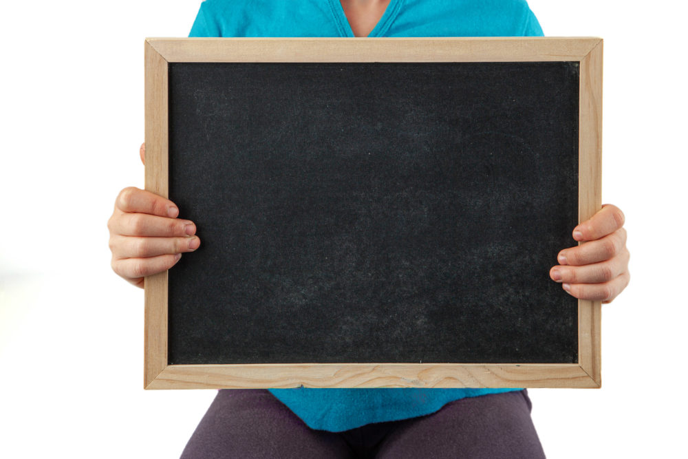 Child midsection holding an empty blackboard with copy space