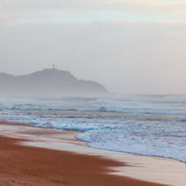 Byron Bay Lighthouse on a cliff disappearing in the morning mist. Byron Bay, New South Wales, Australia