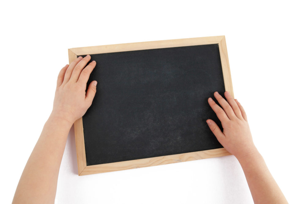 op view of child hands and empty chalkboard isolated on white