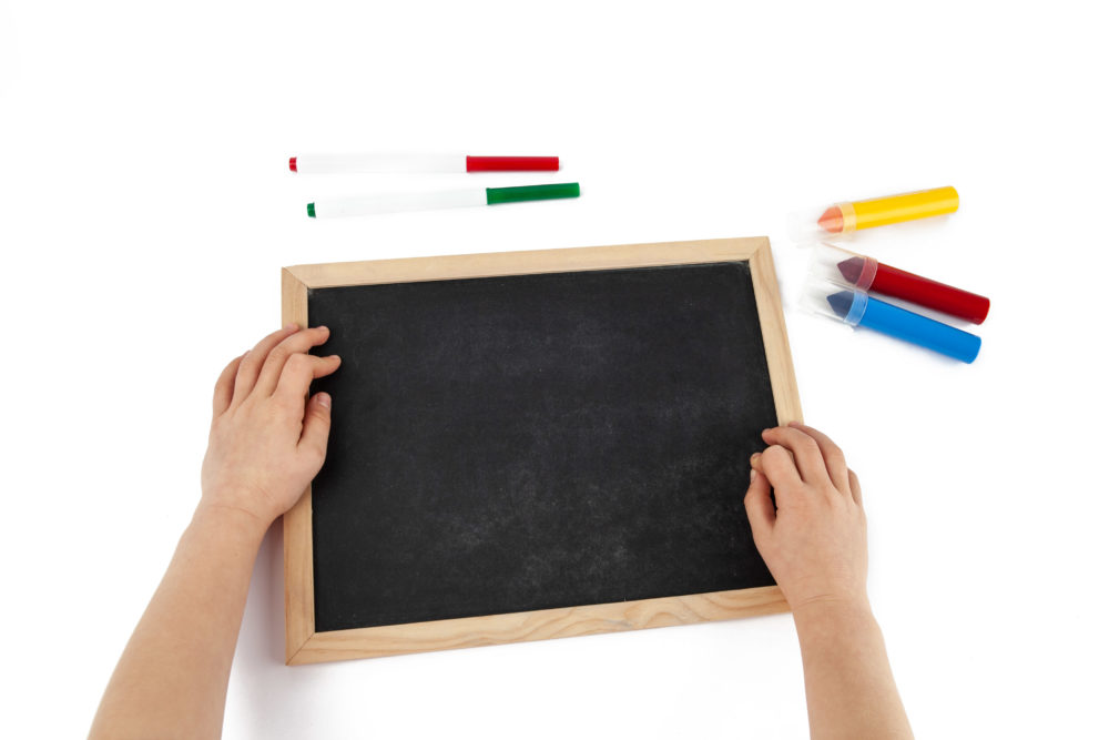 Top view of child hands and empty chalkboard with colorful markers laying around isolated on white