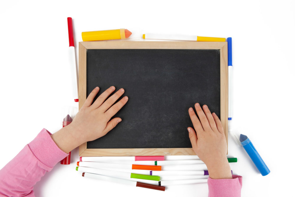 Child hands on empty chalkboard with colorful markers laying around isolated on white