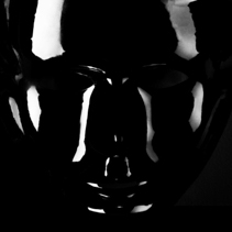 Shiny black mask silhouette on pitch black background.