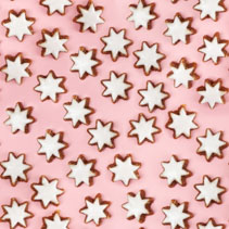 Almond stars biscuits with sugar icing on pink background - seamless pattern