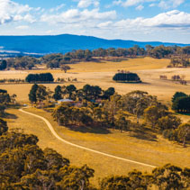 Scenic Australian countryside with winding dirt road. Macedon Ranges, Melbourne, Australia