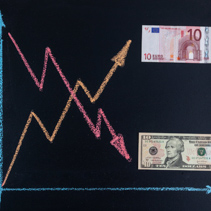 Forex currency trends concept - USD going down while EUR going up. Depicted with chalkboard line graph and paper currency.