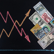 International currency rates trends concept - line graph with arrows pointing up and down drawn with chalk on blackboard and paper money bills AUD, USD, EUR arranged