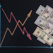 US dollars currency rates trends concept - line graph with arrows pointing up and down drawn with chalk on blackboard and arrangement of paper money bills