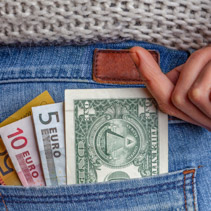 Internet business, profits, travel and finance concept - USD, AUD, and EUR in back pocket of blue jeans with female hand reaching for the money