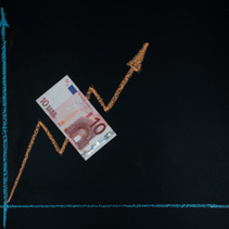 Currency forex trends market concept - upward trend depicted with line graph pointing up drawn with chalk on blackboard and 10 Euro bill with copy space