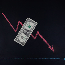 Currency forex trends concept - downward trend depicted with line graph pointing down drawn with chalk on blackboard and one dollar bill with copy space