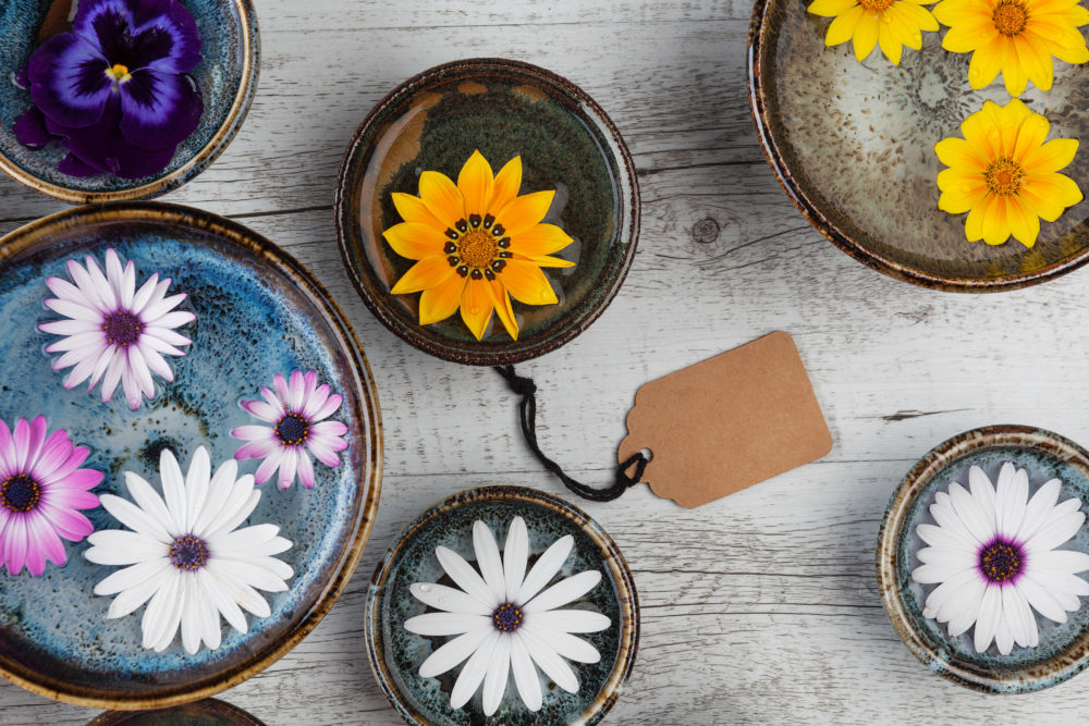 Elegant and colorful flowers floating in water in ceramic bowls on rustic wooden table with gift tag. Closeup, top view with copy space.