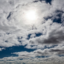 White fluffy clouds covering bright sun in skies - background pattern