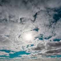 Clouds covering bright sun in the sky - background