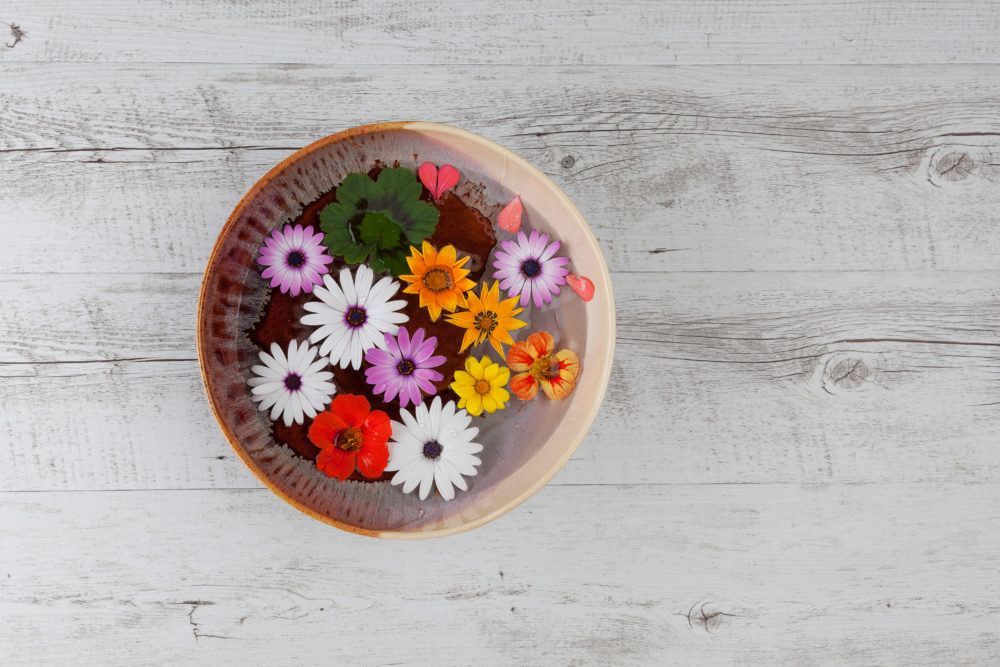 Colorful flowers floating in big ceramic bowl filled with water on white rustic wooden table. Top view with copy space.