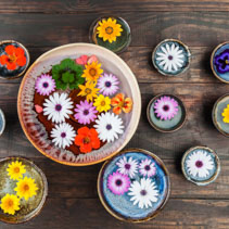Beautiful floral composition with colorful flowers floating in water on dark wooden table. Top view.