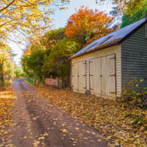 Autumn landscape with road and a barn