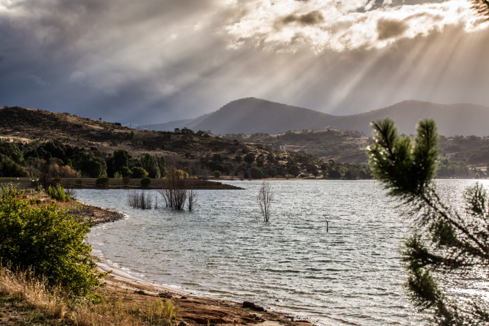 Sun Rays shining through clouds on the Hills of Lake Jindabyne,
