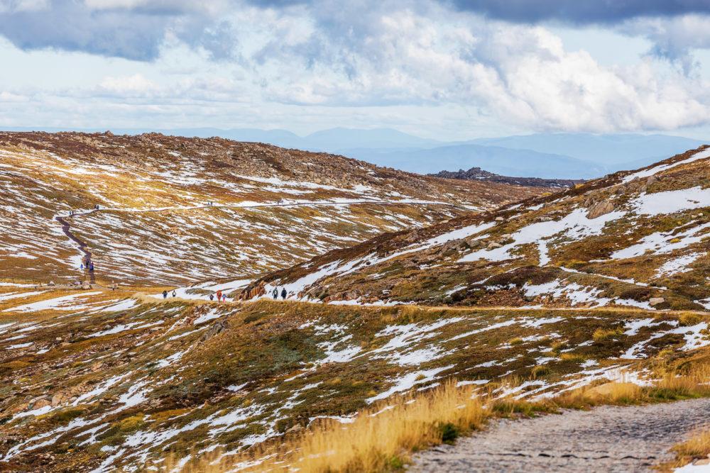 People walking on Mount Kosciuszko summit walk. Snowy Mountains,