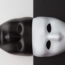 Black and white masks joined on contrasting background. Anonymity concept.