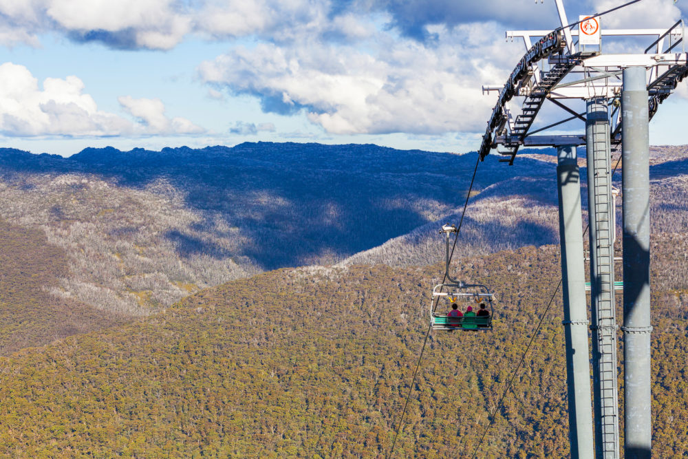 People sitting on Kosciuszko Express Chairlift in front of beaut