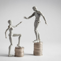 Income inequality concept shown with realistic male and female figurines and piles of coins. Female figurine extending hand towards male