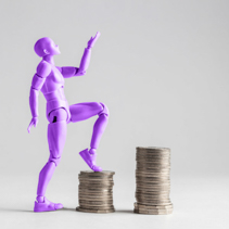 Empowered women stepping up the income ladder concept. Purple female figurine climbing up on piles of coins. Isolated on white with copy space.