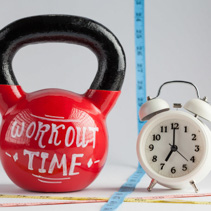 Red kettlebell with Workout Time lettering, traditional alarm clock, and measuring tape isolated on white