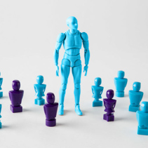 Strong male figurine standing among faceless lookalike figurines. Search for identity, stand out of the crowd concepts