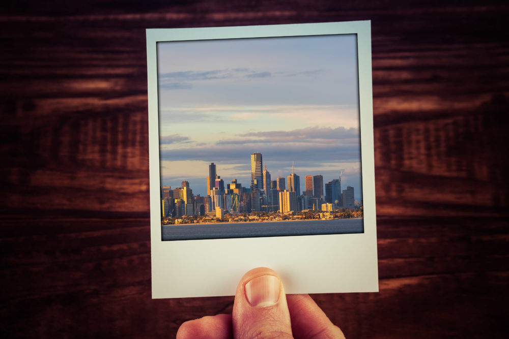 Photograph of Melbourne skyline from waterfront held by male han