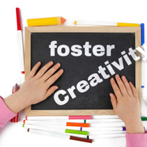 Child hands placed on blackboard with text foster Creativity among colorful markers scattered on the table