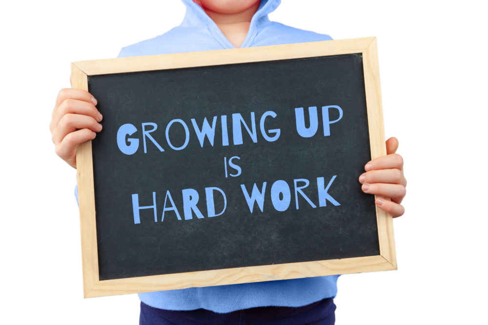 The topic of Growing Up depicted with child holding blackboard saying Growing Up Is Hard Work