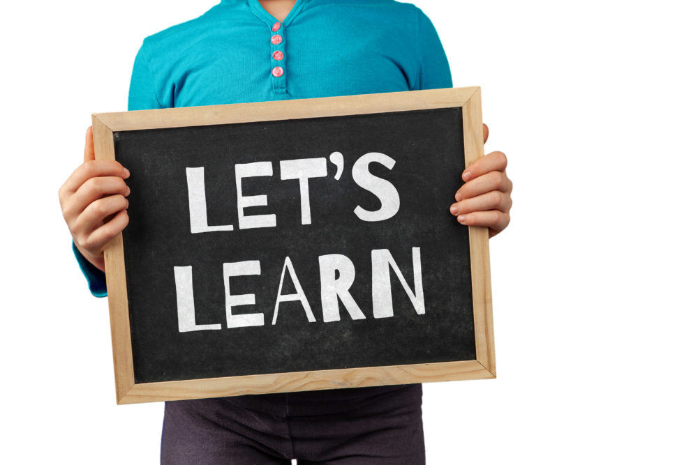 Education topic depicted with child holding blackboard with text Let's Learn