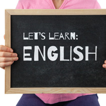 Child midsection holding blackboard with Let's Learn English text