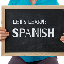 Child holding blackboard with Let's Learn Spanish text
