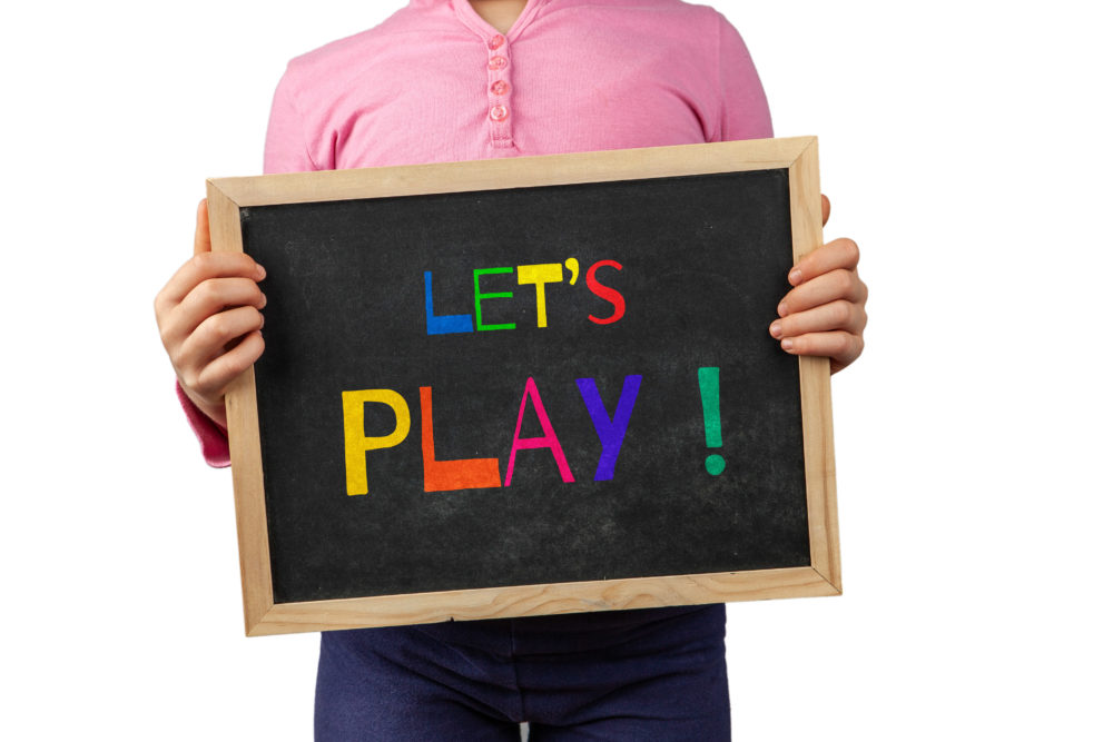 Child holding blackboard saying Let's Play!