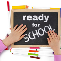 Getting ready for school concept depicted with child hands on blackboard with text - top view