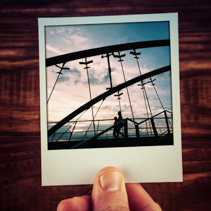 Hand holding instant photo of two people silhouettes walking on