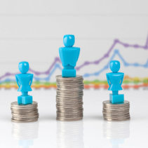 One male and two female figurines standing on piles of coins with line graph in the background. Income inequality concept.