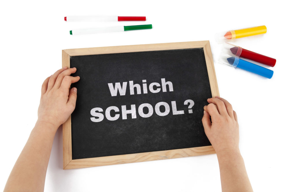 Choosing a school for your child problem depicted with childs hand and chalkboard with text.